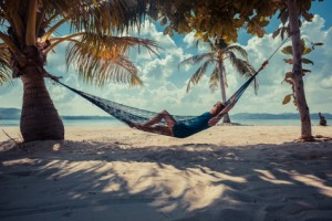 A young woman is relaxing in a hammock on a tropical beach