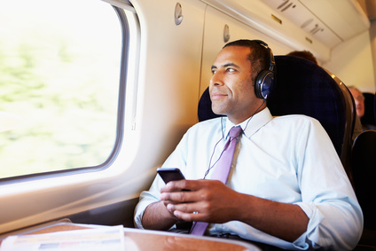 Businessman Relaxing On Train Listening To Audio Books