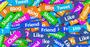 Social media concept background with a moltitude of social network words signs and text on scattered colorful paper.