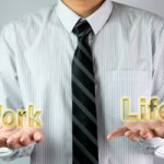 Businessman with open hands palm balancing the word work and life