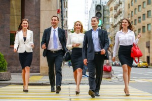 Team of five business people confidently striding along the summ