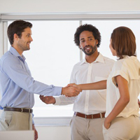 Business people shaking hands besides colleague at office