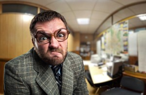 Angry businessman in glasses looking at you